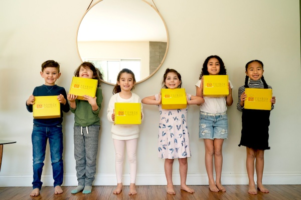 5 girls and 1 boy lined up, holding a yellow subscription box and smiling widely.