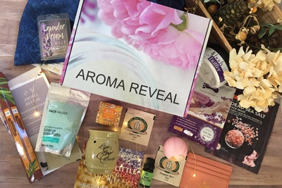 An Aroma Reveal subscription box with a pink flower, incense, a bath bomb, and scented sea salts.