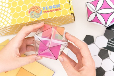 Hands holding an origami hexagon shape and a yellow Flock Eco Games subscription box.