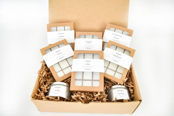 A plain brown subscription box filled with Design Undone wax melts and candles.