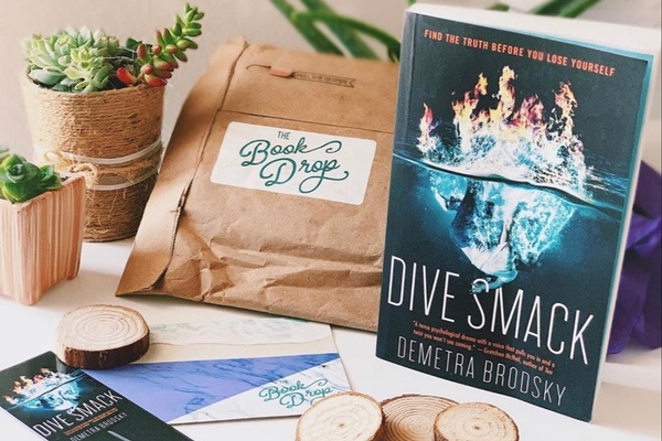 The Book Drop package with Dive Smack book displayed, and decorative succulents.