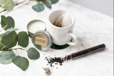 A white mug with tea and a tea bag in it, next to a small candle, some leaves, and a vial with tea leaves in it.