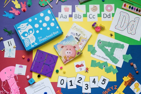 A table covered with arts and crafts, letters and numbers, and a blue preschool subscription box.