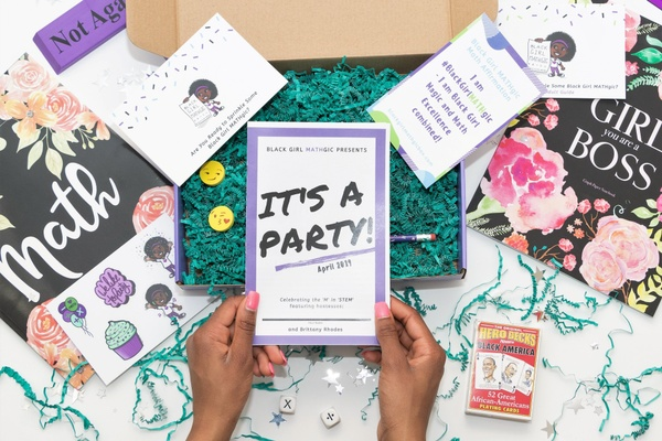 A girls hands hold a book titled It's A Party! next to a subscription box with encouraging cards and a magic deck of cards.