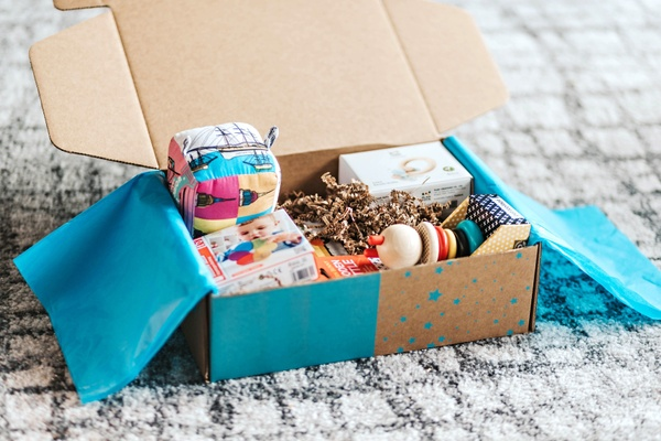 Open subscription box with baby and toddler toys shown.