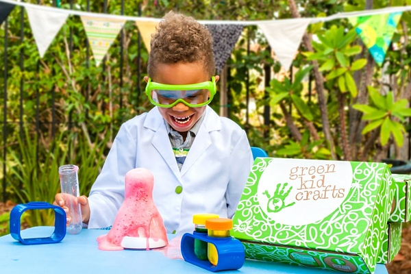 Next to a Green Kid Crafts subscription box, a child wearing green goggles laughs while pink foam spills out of a beaker.