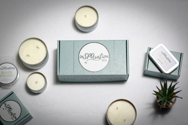 A sage green InSPArations subscription box surrounded by candles in tins and a small potted plant.