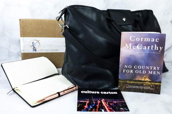 An open, blank journal with a pen, a large black bag, the book No Country for Old Men, and a card that says Culture Carton.